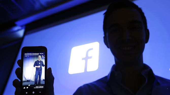 Michael Goodwin, Senior Partner for HTC, displays an HTC First cell phone wit the new Facebook interface at Facebook headquarters in Menlo Park, Calif., Thursday, April 4, 2013.   The company  says it is not building a phone or an operating system. Rather, Facebook is introducing  a new experience for Android phones. The idea behind the new Home service is to bring content right to you, rather than require people to check apps on the device.   (AP Photo/Marcio Jose Sanchez)