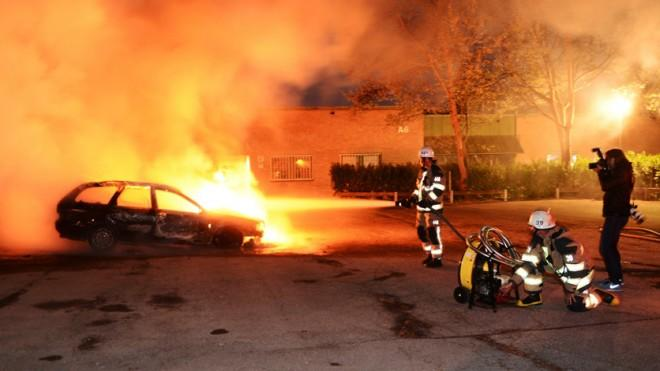 Firefighters extinguish a burning car on May 21, following riots in the Stockholm suburb of Kista.