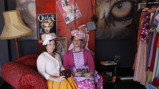 "In this photo taken Thursday, Jan. 10, 2013 visitors Yolandi Gloy, left, and Elize van der Nest, right, are photographed in period costume on the film set turned theme park, of the Afrikaans musical film ""Pretville"" in Hartebeespoort, South Africa. The movie indulges in rock'n roll, vintage cars, greasers in sneakers, pin curl hairstyles and swing dresses, lots of pastel pink and blue, and double-thick strawberry milkshakes with extra cream. (AP Photo/Denis Farrell)"