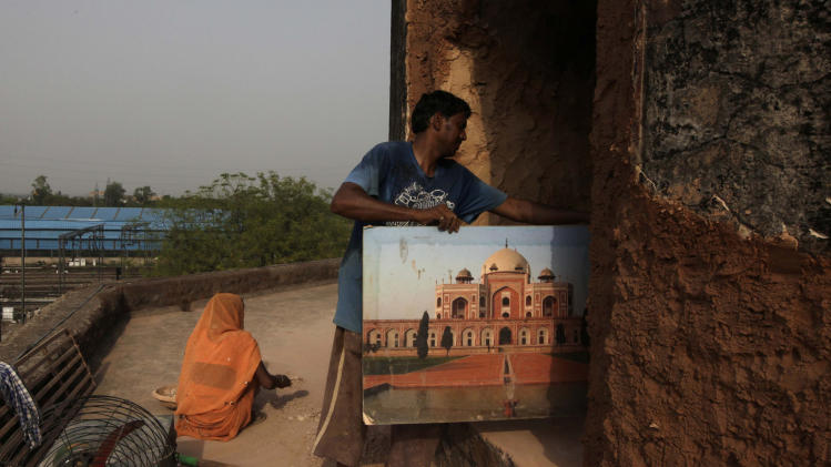 In this Friday, June 7, 2013 photo, an Indian worker holds a portrait of the tomb of Emperor Humayun as he works on renovation of the Neela Gumbad, or Blue Tomb, as part of a project for the creation of a mammoth, iconic park that would rival New York's Central Park as a refuge from urban chaos, in New Delhi, India. To create that park would require the merger of a string of adjoining gardens, heritage areas and a zoo administered by different government agencies, an incredibly complicated task in a land where bureaucratic turfs are fiercely protected. It would be 1,200 acres, considerably larger than Central Park. It would encompass one of the most impressive collections of medieval Islamic monuments, anchored by the grandiose tomb of Emperor Humayun, a 16th Century prototype for the Taj Mahal. (AP Photo/Manish Swarup)
