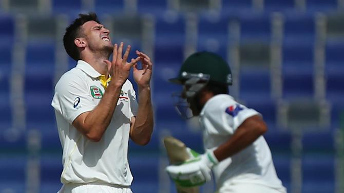 Australian bowler Mitchell Marsh reacts as Pakistani batsman Younis Khan runs between wickets during the second day of the second Test in Abu Dhabi on October 31, 2014