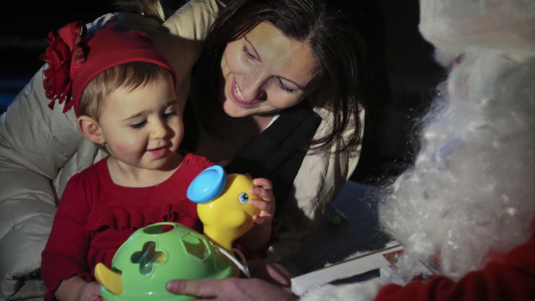 In this Tuesday, Dec. 18, 2012 photo, Elizabeth Sampol holds her daughter Ella, 14 months, who received a toy from Michael Sciaraffo, as Santa,  in the Belle Harbor neighborhood of the Queens borough of New York. Using Facebook, Sciaraffo started a charitable enterprise to collect and personally deliver toys to children affected by Superstorm Sandy, dressed as Santa Claus.  (AP Photo/Bebeto Matthews)
