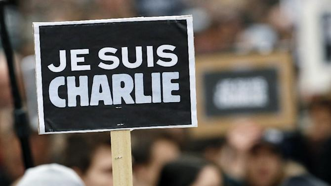 "People hold a poster reading ""Je suis Charlie (I am Charlie)"" during a rally in Paris on January 11, 2015 in tribute to the 17 victims of a three-day killing spree by homegrown Islamists"