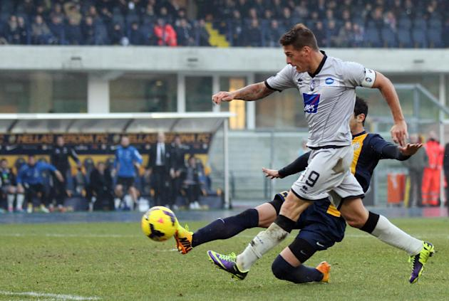 Atalanta's forward German Denis, of Argentina, foreground, scores during a Serie A soccer match against Hellas Verona, at the Bentegodi stadium in Verona, Italy, Sunday, Dec. 8, 2013