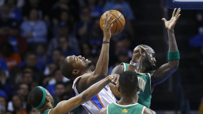 Oklahoma City Thunder forward Kevin Durant, with ball, is fouled by Boston Celtics forward Paul Pierce (34) as he shoots among Pierce, forward Kevin Garnett (5) and forward Jeff Green (8) in the second quarter of an NBA basketball game in Oklahoma City, Sunday, March 10, 2013. (AP Photo/Sue Ogrocki)