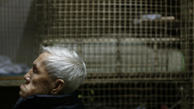 In this Jan. 25, 2013 photo, 77-year-old Yeung Ying Biu sits next to the cage, measuring 1.5 square meters (16 square feet), he calls home, in Hong Kong.  For many of the richest people in Hong Kong, one of Asia's wealthiest cities, home is a mansion with an expansive view from the heights of Victoria Peak. For some of the poorest, home is a metal cage. Some 100,000 people in the former British colony live in what's known as inadequate housing, according to the Society for Community Organization, a social welfare group. (AP Photo/Vincent Yu)