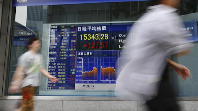 People walk past an electronic stock indicator in Tokyo, Tuesday, July 22, 2014. Asian shares rose Tuesday as tensions over the downing of a passenger jet in Ukraine eased after pro-Moscow separatists released a train packed with bodies and handed over the aircraft's black boxes. Japan's Nikkei 225 stock index added 0.8 percent to 15,343.28 as trading resumed after Monday's public holiday. (AP Photo/Shizuo Kambayashi)