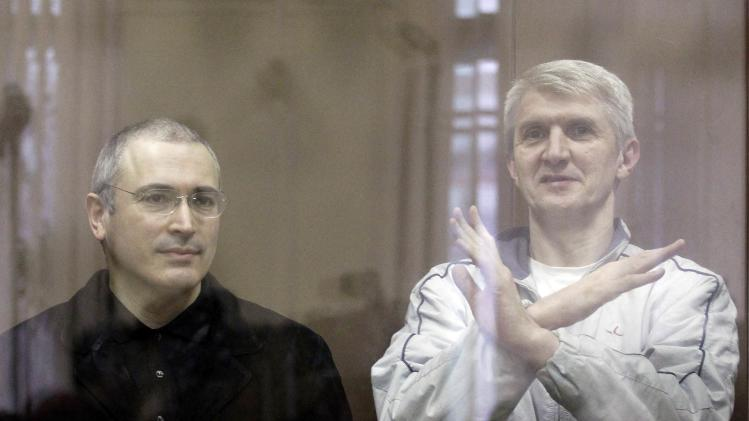 File photo of then jailed Russian former oil tycoon Khodorkovsky and his business partner Lebedev standing behind a glass wall during a court session in Moscow