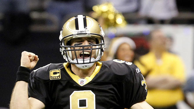 New Orleans Saints quarterback Drew Brees celebrates a touchdown by running back Pierre Thomas in the first quarter of an NFL football game against the Atlanta Falcons in New Orleans, Monday, Dec. 26, 2011. (AP Photo/Bill Haber)