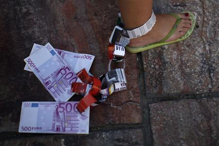 A demonstrator hangs fake Euro notes on her leg during a protest against Spain's bailout in Malaga