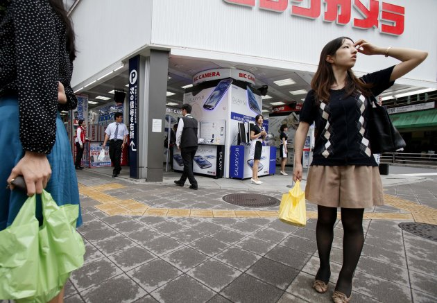A woman waits at a crosswalk in front of a large retail store in Tokyo Monday, July 2, 2012. Big manufacturers have more confidence in Japan's economy but remain pessimistic overall, a closely watched quarterly survey by the country's central bank showed Monday. (AP Photo/Koji Sasahara)
