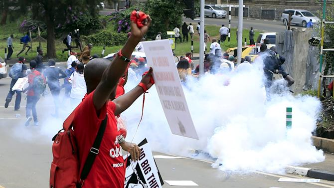 People run from tear gas fired by the police during a street protest on corruption in Kenya's capital Nairobi