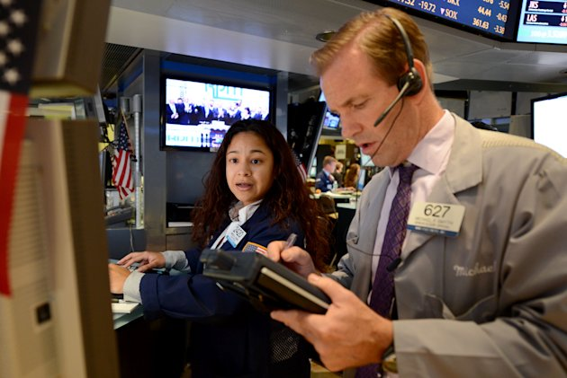 Wingszi Chang, left, of Getco Securities, and Michael Smyth of MND Partners trade on the floor of the New York Stock Exchange Monday, July 23, 2012 in New York. The Dow Jones industrial average closed