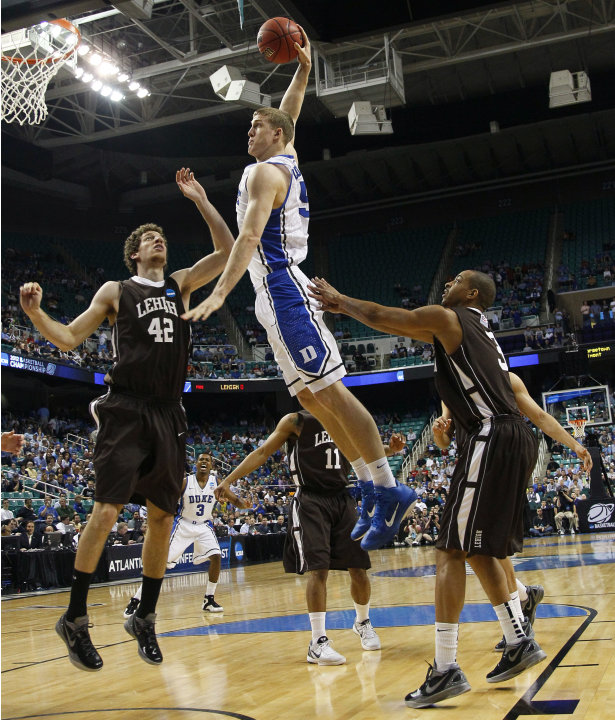 Duke's Mason Plumlee (5) goes up to dunk as Lehigh's Gabe Knutson (42) and C.J. McCollum (3) defend during the first half of an NCAA tournament second-round college basketball game in Greensbo