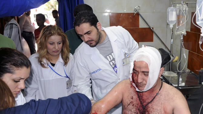 In this photo released by the Syrian official news agency SANA, Syrian doctors treat an injured man who was wounded by a car bomb, at Jaramana neighborhood, in Damascus, Syria, Monday Oct. 29, 2012. A Syrian government official says a car bomb in a Damascus suburb has killed 10 people. The official said the blast on Monday in Jaramana also wounded 41 people and caused heavy damage. He spoke on condition of anonymity because he was not authorized to speak to the media. (AP Photo/SANA)