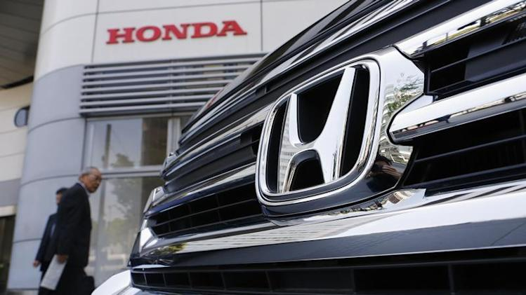 Visitors look at a Honda Motor Co's car displayed outside the company showroom in Tokyo
