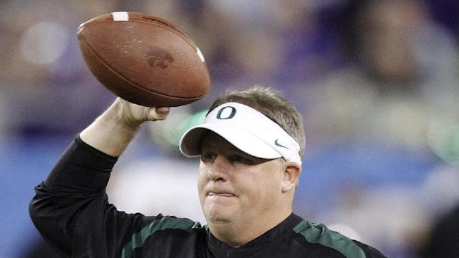 Oregon head coach Chip Kelly tosses a football to a Kansas State player during warmups before the Fiesta Bowl NCAA college football game, Thursday, Jan. 3, 2013, in Glendale, Ariz. (AP Photo/Paul Connors)