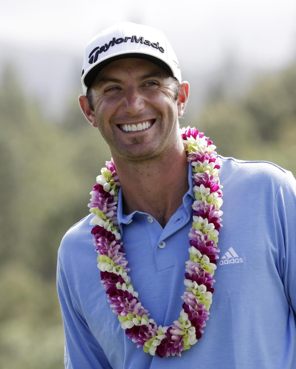 File-This Jan. 8, 2013 file photo shows Dustin Johnson smiling as he waits to receive the championship trophy after winning the Tournament of Champions PGA golf tournament in Kapalua, Hawaii. PGA Tour player Dustin Johnson and Paulina Gretzky have taken to Twitter to say they're getting married. (AP Photo/Elaine Thompson, File)