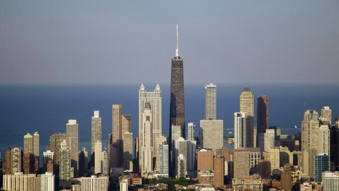 FILE-This Friday, June 15, 2012, file photo, shows the Chicago skyline. The Chicago area's jobless rate improved to 9.4 percent in June from 10.9 percent a year earlier. Sales of foreclosed homes have been climbing. The region's supply of bank-owned homes is now nearly 19 months. (AP Photo/Carolyn Kaster)