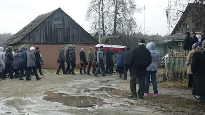 Men carry a coffin during the funeral of Russian serviceman Fyodor Zhuravlyov near a cemetery in the village of Paltso