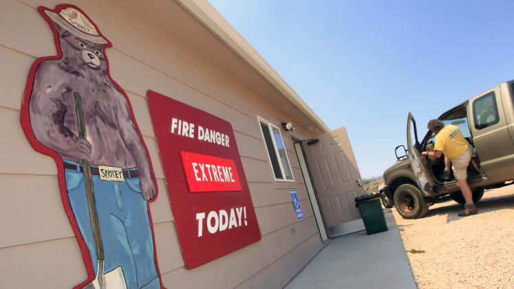 "A sign with the character ""Smokey The bear"" warns of extreme fire danger as a wildfire continues to burn near Livermore, Colo., on Saturday, June 23, 2012. Authorities sent out 992 evacuation notices Friday due to the wildfire burning on more than 100 square miles in northern Colorado as winds pick up. (AP Photo/David Zalubowski)"