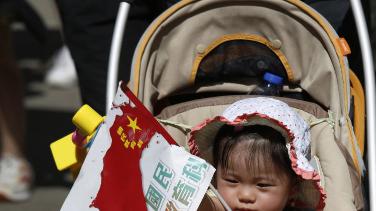 """A child holds a distorted Chinese national flag with a slogan """"Withdraw chinese patriotism classes"""" on a stroller pushed by a parent during a march on a downtown street in Hong Kong  Sunday, July 29, 2012, to protest the upcoming introduction in schools of Chinese patriotism classes that they fear will lead to brainwashing. Teachers, parents, students and pro-democracy activists marched Sunday to the government headquarters of the semiautonomous territory to protest against the new curriculum, which authorities are encouraging schools to begin using when classes resume in September. (AP Photo/Vincent Yu)"""