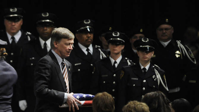 Colorado Gov. John Hickenlooper brings a folded flag to the family of Tom Clements during the public memorial for the chief executive of the Department of Corrections at New Life Church in Colorado Springs, Colo on Monday, March 25, 2013. Clements was shot and killed on the doorstep of his Monument, Colo. home last week. (AP Photo/The Gazette, Jerilee Bennett, Pool)