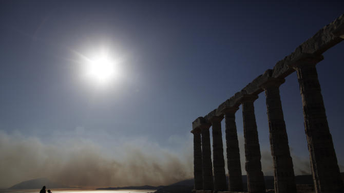 Visitors stand next to the ruins of the 5th century B.C. Temple of Poseidon as smoke from a fire rises over the Saronic Gulf at Cape Sounion, south of Athens, Saturday, June 16, 2012. A fire aided by strong winds has burned grassland and threatened houses near the town of Keratea, 50 kilometers (30 miles) south of Athens. The fire started in the early Saturday afternoon on dried grass, apparently as the result of an accident and has been spreading fast, threatening to engulf isolated houses on the outskirts of the towns of Keratea and Palea Fokaia. (AP Photo/Kostas Tsironis)