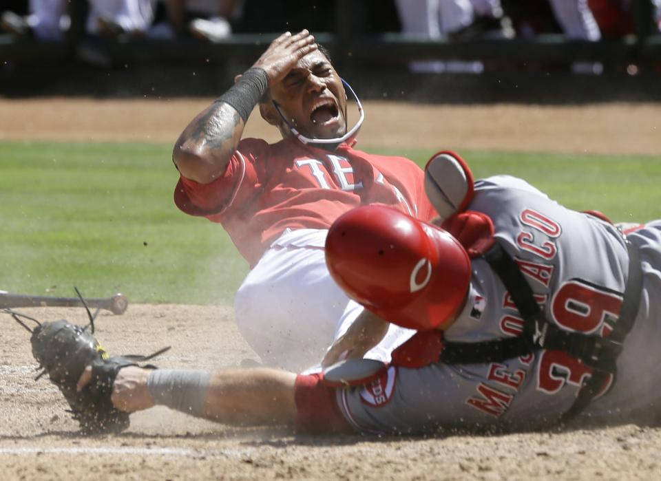 Texas Rangers' Engel Beltre, left, reaches to his face in pain after a collision with Cincinnati Reds' Devin Mesoraco, right, on a scoring play in the fifth inning of a baseball game Sunday, June 30, 2013, in Arlington, Texas. (AP Photo/Tony Gutierrez)