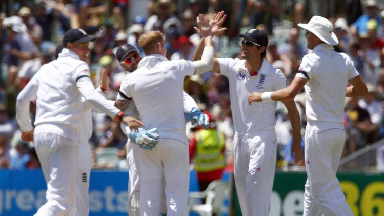 England's Stokes celebrates with captain Cook and team-mates after taking the wicket of Australia's captain Clarke during second day's play in second Ashes cricket test at Adelaide Oval