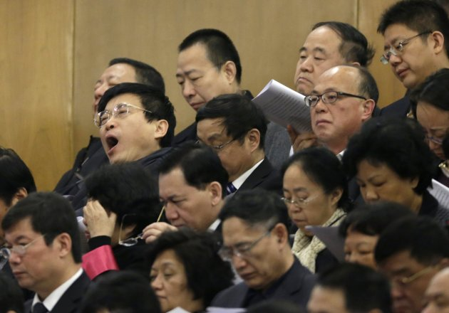 A delegate yawns as 2012 Nobel Prize Laureate for Literature Mo Yan looks on, at the Great Hall of the People in Beijing