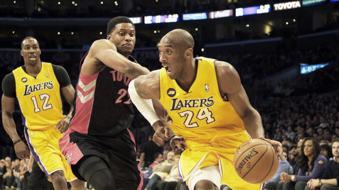 Los Angeles Lakers guard Kobe Bryant (24) drives past Toronto Raptors forward Rudy Gay (22) in the first half of an NBA basketball game in Los Angeles Friday, March 8, 2013. (AP Photo/Reed Saxon)