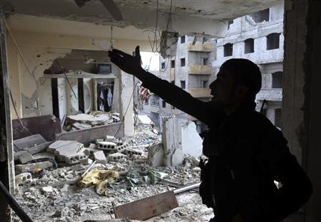 A Free Syrian Army fighter gestures in a building damaged by Syrian Army tank shells in the Arabeen neighbourhood of Damascus January 24, 2013. REUTERS/Goran Tomasevic