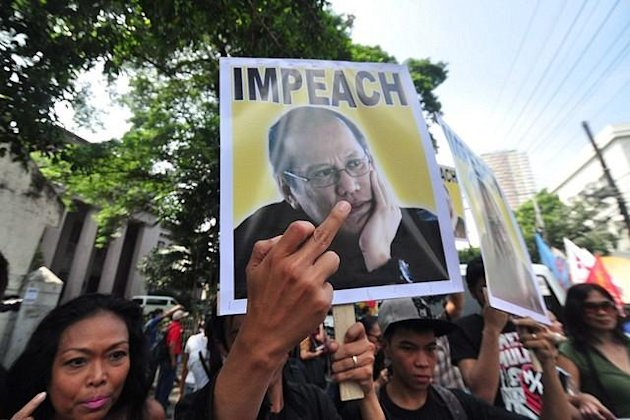 Protesters throw dirty fingers at the portrait of President Noynoy Aquino seen during the anti Cybercrime Law protest held in front of the Supreme Court in Manila on 09 October 2012. (George Calvelo/NPPA Images)
