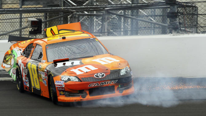 Kyle Busch (18) slides along the wall during a NASCAR Sprint Cup Series auto race at Kansas Speedway in Kansas City, Kan., Sunday, Oct. 21, 2012. (AP Photo/Colin E. Braley)