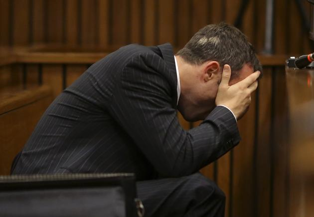Olympic and Paralympic track star Oscar Pistorius reacts as he reaches for a bucket in the dock during his trial for the murder of his girlfriend Reeva Steenkamp, at the North Gauteng High Court in Pr