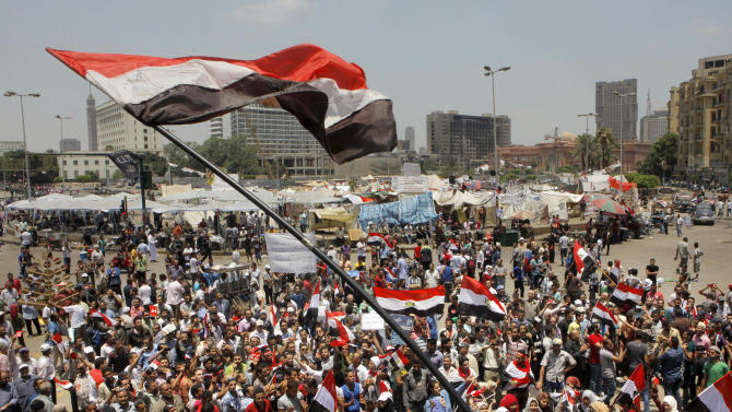 Egyptian protesters shout slogans and wave national flags during a demonstration against Egypt's Islamist President Mohammed Morsi in Tahrir Square in Cairo, Monday, July 1, 2013. Elsewhere in Cairo, protesters stormed and ransacked the headquarters of President Mohammed Morsi's Muslim Brotherhood group early Monday, in an attack that could spark more violence as demonstrators gear up for a second day of mass rallies aimed at forcing the Islamist leader from power. (AP Photo/Amr Nabil)