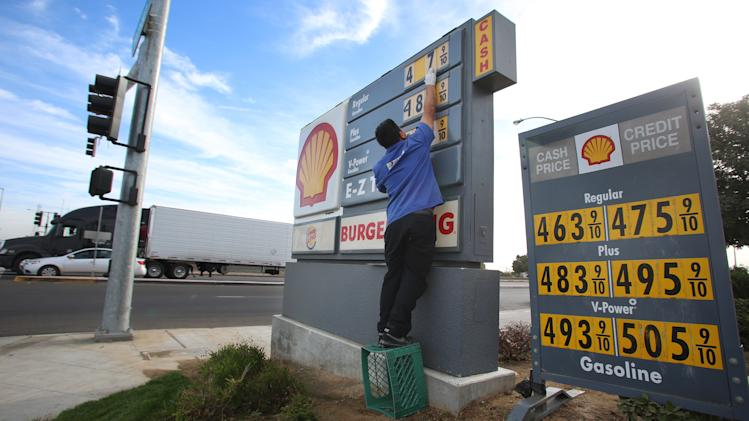 FILE- In this Friday, Oct. 5, 2012, file photo, Luis Cuevas changes the gas prices at the Shell station off California State Route 99. Forecasters say that ample oil supplies and weak U.S. gasoline demand will keep a lid on prices in 2103. The lows will be lower, the highs won't be so high, and the average price of a gallon of gasoline will fall 5 percent to $3.44, according to the Energy Department. (AP Photo/Gary Kazanjian, File)