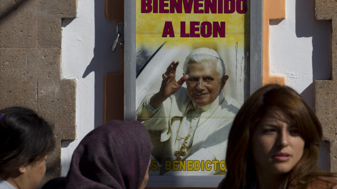 Pedestrians walks past a poster with an image of a waving Pope Benedict XVI, in Leon, Mexico, Thursday March 22, 2012. It's been a decade since the former Pope John Paul Paul II visited Mexico; his fifth and final trip to the country. His successor, Benedict, arrives Friday. The Pope will hold Sunday Mass in Silao, Mexico, against the backdrop of the 60-foot-tall hilltop statue of Christ the King, before leaving for Cuba on Monday. (AP Photo/Eduardo Verdugo)