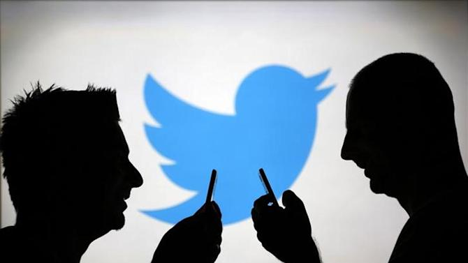 Men are silhouetted against a video screen with a Twitter logo as he poses with a Samsung S4 smartphone in this photo illustration taken in the central Bosnian town of Zenica, August 14, 2013. REUTERS/Dado Ruvic/Files