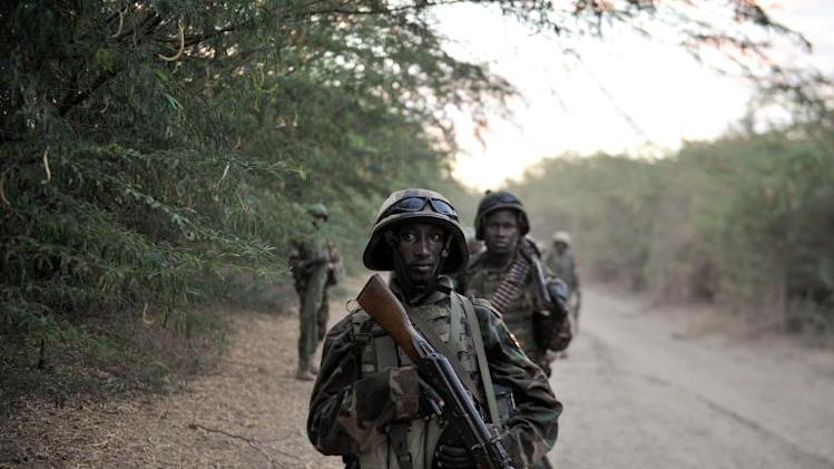 A handout photo released by the African Union-United Nations Information Support team shows Ugandan soldiers of the African Union Mission in Somalia take a break as they march toward the town of Qoryooley, Somalia, on March 22, 2014