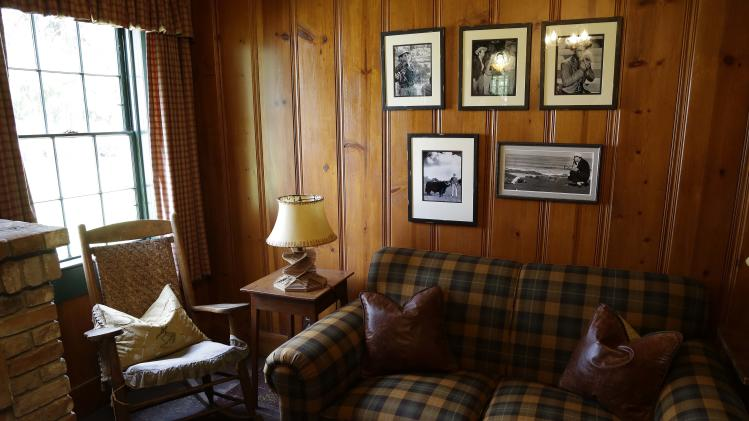 """In this photo taken March 15, 2013 a selection of old photographs hang in a study beside actor Fred MacMurray's rocking chair at the MacMurray Ranch in Healdsburg, Calif. The former cattle ranch, which was purchased in 1941 by the actor in the popular TV series """"My Three Sons,"""" now produces wine and is owned by the Gallo wine family. (AP Photo/Eric Risberg)"""