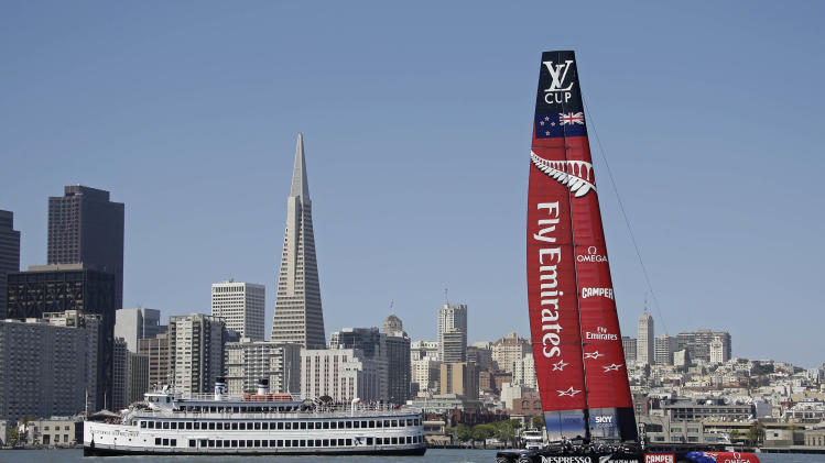 Emirates Team New Zealand sails past the Transamerica Pyramid and a bay cruise boat during training for the America's Cup Friday, May 24, 2013 in San Francisco. (AP Photo/Eric Risberg)