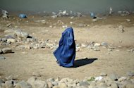 A burqa-clad woman walks through a park in the Afghan capital Kabul. Afghan police are hunting a man who allegedly killed his wife after she gave birth to the couple's third daughter, an official said