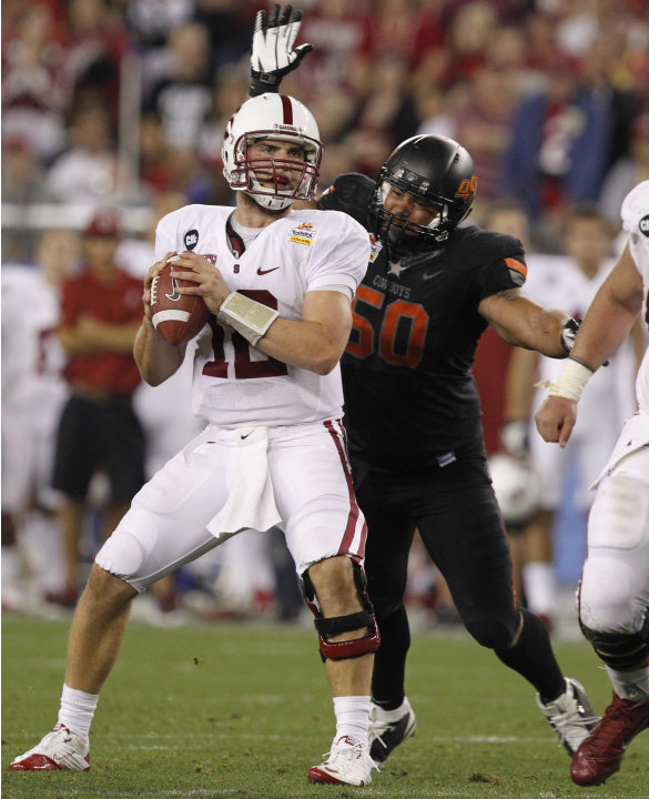 Stanford quarterback Andrew Luck (12)  looks downfield just before getting sacked by Oklahoma State defensive end Jamie Blatnick (50) during the second half of the Fiesta Bowl NCAA college football ga