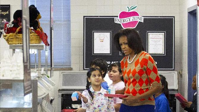 FILE - This Jan. 25, 2012 file photo shows first lady Michelle Obama having lunch with school children at Parklawn elementary school in Alexandria, Va.  Obama has proven her fashion savvy time and time again since she was introduced to the country as first lady on Inauguration Day 2009. In the past four years she has adeptly walked the line between directional fashionista and everywoman. (AP Photo/Pablo Martinez Monsivais)