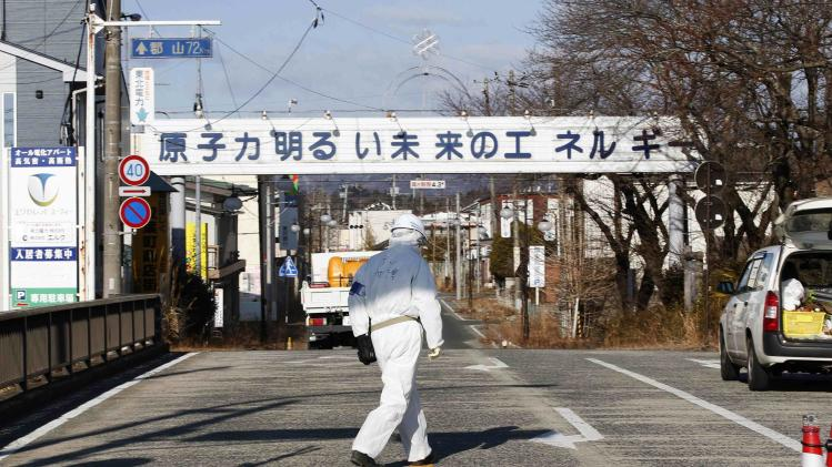 A decontamination worker walks at the entrance of the empty Futaba town