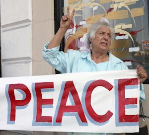 Anti-war activist Joyce Brody rallies for peace outside the offices of Rep. Adam Schiff (D-CA), a senior member of the Intelligence Committee, to urge him to vote against a possible limited military strike on Syria in Hollywood selection of Los Angeles Tuesday, Sept 10, 2013. In the run-up to a prime-time televised speech, President Barack Obama blended the threat of a military strike with the hope of a diplomatic solution Tuesday as he worked to rid Syria of an illicit stockpile of fearsome chemical weapons. (AP Photo/Nick Ut)