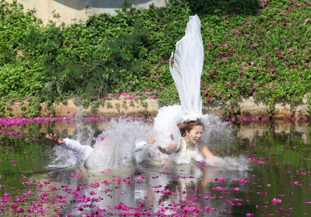 Thai groom Sopon Sapaotong and his bride Chutima Imsuntear jump in a pond during a wedding ceremony in Prachin Buri province