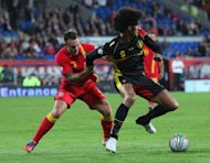 Wales' Darcy Blake (L) vies for the ball with Belgium's Marouane Fellaini (R) during the 2014 World Cup qualifying football match between Wales and Belgium at Cardiff City Stadium in Cardiff. Belgium won a comfortable 2-0 win over Wales
